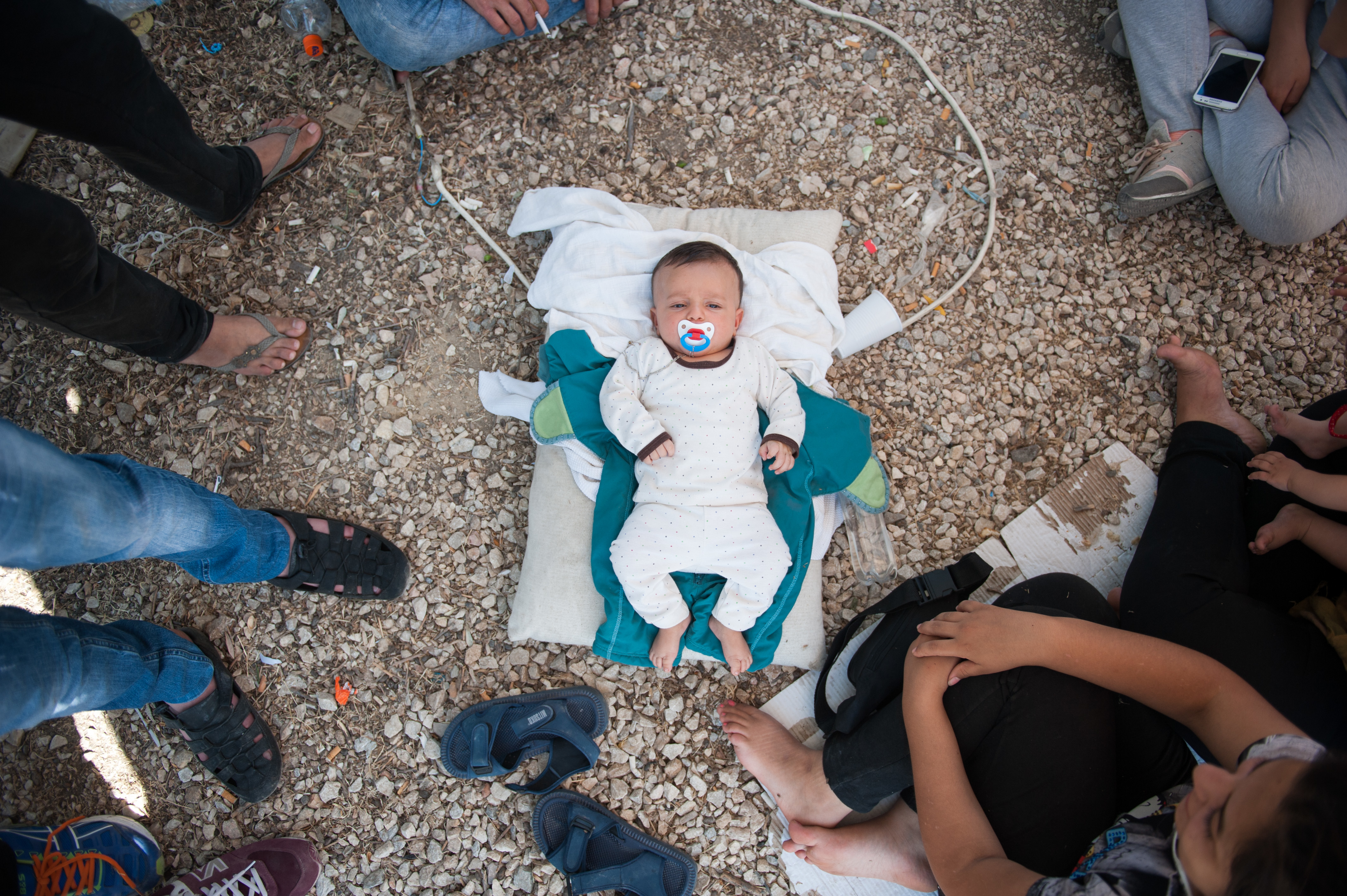 """A Syrian baby lies in the floor of Kara Tepe camp. The family has no milk to feed the child and no money to buy.  The baby's father, 26 year old  Deshevan said:  """"I am here with my family: my wife, my child and my sister. We are part of a group of 19 people from Syria.  We have been in the camp for five days so far. There is nothing here for us. All 19 of us sleep in one tent. Everywhere you see dirty water and rubbish. There are no toilets, no cleanliness. There is one small tap for drinking water and washing ourselves.  There is not enough food for everyone, but this is not important to us. What we need – but don't have – is information about our papers.   We were given a piece of paper by the port police, but since then we have been waiting here and have heard nothing. Nobody tells us anything. There is no one responsible to give us any information, and we don't know what to do. No authority, no police, no information, nothing.  There is no milk for the baby – no one has given us any – so we have to go to the supermarket and buy it. We don't have enough money, but for the baby we will find a way."""""""