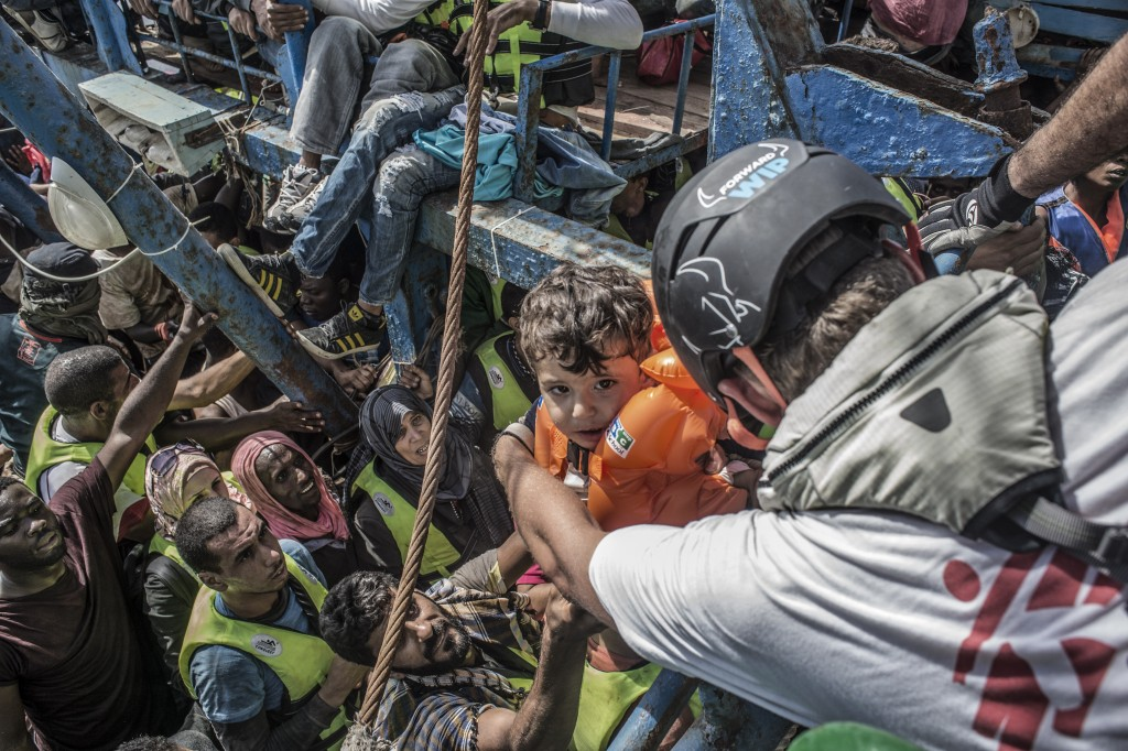 26th August 2015. A young child is lifted from a boat containing approximately 650 people by Sebastian Stein (MSF Coordinator) during a rescue in the Mediterranean Sea by the Bourbon Argos.