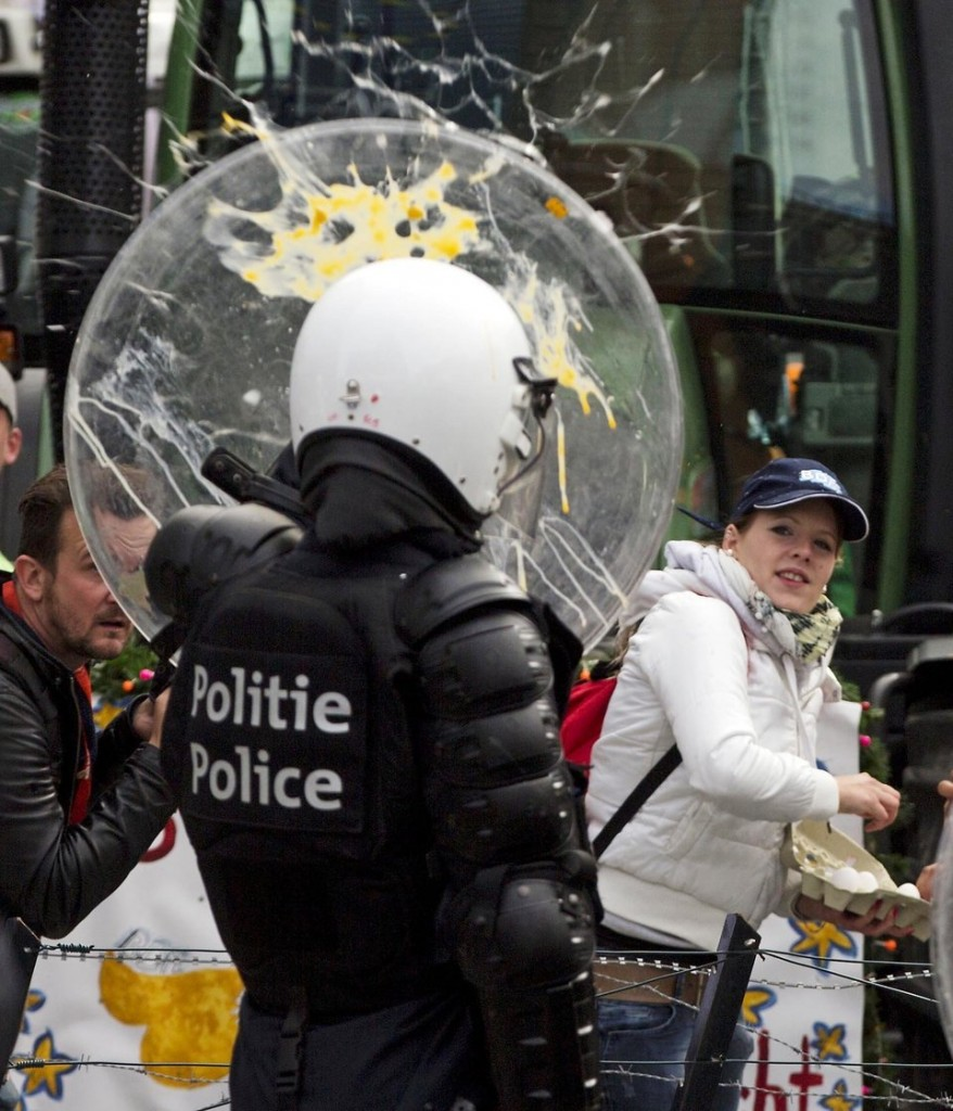 A woman throws eggs at riot police during a farmers demonstration in Brussels on Monday, Sept. 7, 2015. European dairy farmers demonstrated in Brussels on Monday to protest against what they believe are unfair prices on their dairy products. (AP Photo/Virginia Mayo)