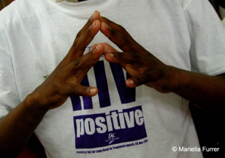 "A young man wearing an ""HIV Positive"" t-shirt puts his hands together for a prayer during Mr Mandela's visit to Siyaphila la HIV Treatment Program hosted by MSF and the Nelson Mandela Foundation. The event was held at the Lusikiki Teacher's Training College."