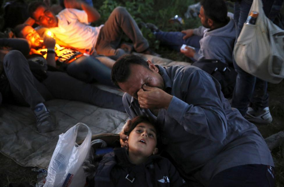 Kurdish Syrian immigrant Sahin Serko cries next to his 7 year-old daughter Ariana minutes after crossing the border into Macedonia, along with another 45 Syrian immigrants, near the Greek village of Idomeni in Kilkis prefecture, May 14, 2015. Hundreds of mostly Afghan, Syrian, and African immigrants cross daily from Greece into Macedonia on their way to northern European countries; most of them are turned back by Macedonian border guards. REUTERS/Yannis Behrakis