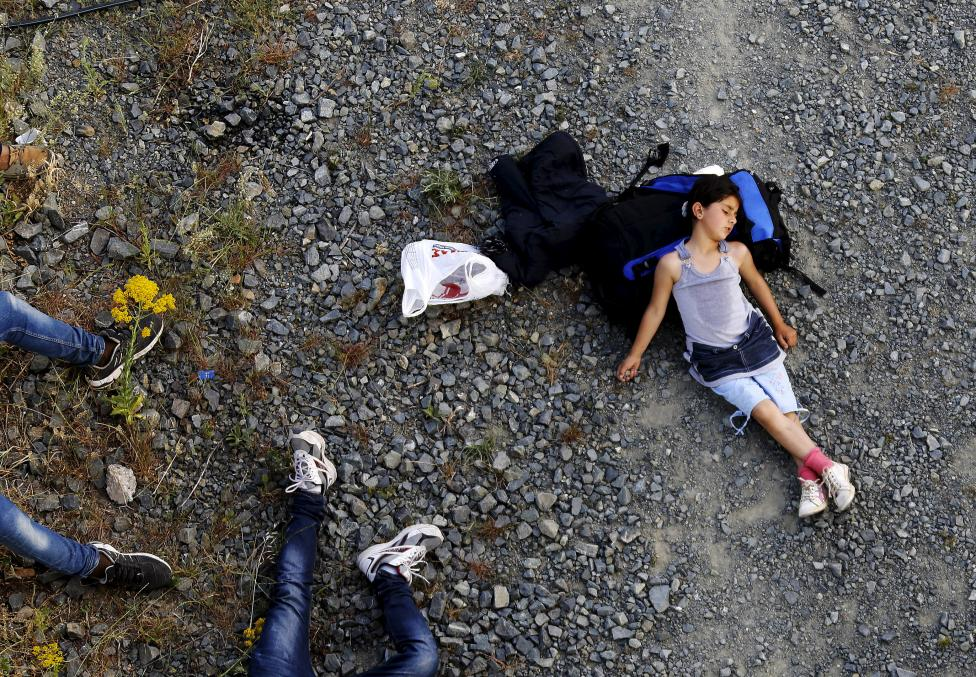 Seven year-old Ariana, a Kurdish-Syrian immigrant, rests before crossing into Macedonia along with another 45 Syrian immigrants near the border Greek village of Idomeni in Kilkis prefecture, May 14, 2015. REUTERS/Yannis Behrakis
