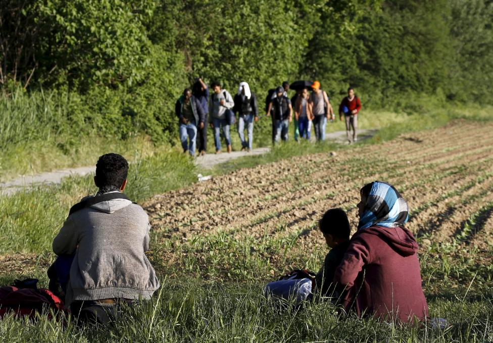 Afghan immigrant family watches a group of Syrian immigrants walk towards Macedonia near the Greek border village of Idomeni in Kilkis prefecture, May 13, 2015. REUTERS/Yannis Behrakis