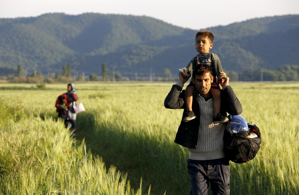 An Afghan immigrant carries his son, followed by his wife, as they walk through a field close to the Greek-Macedonian border in an attempt to flee to Macedonia from the border village of Idomeni in Kilkis prefecture, May 13, 2015. REUTERS/Yannis Behrakis