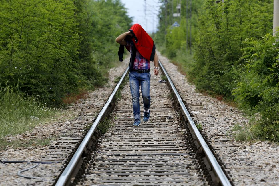 An Afghan immigrant walks on rail tracks back to Greek soil after an unsuccessful attempt to flee to Macedonia from the border village of Idomeni in Kilkis prefecture May 13, 2015. REUTERS/Yannis Behrakis