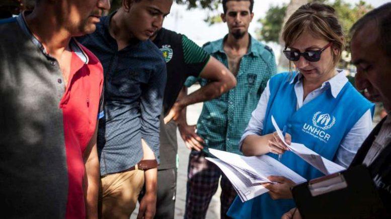 Στέλεχος του Προσωπικού της Ύπατης Αρμοστείας του ΟΗΕ για τους Πρόσφυγες βοηθά πρόσφυγες και μετανάστες να καταχωρήσουν τα στοιχεία τους στο τοπικό αστυνομικό τμήμα στο νησί της Κω, Ελλάδα. Φωτογραφία: UNHCR/S. Baltagiannis.