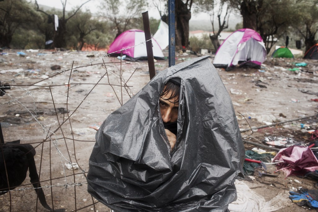 An Afghan refugee wears a rubbish bag to keep himself dry during a rainstorm at the Moria Reception Centre while he waits for his documents on the island of Lesbos.