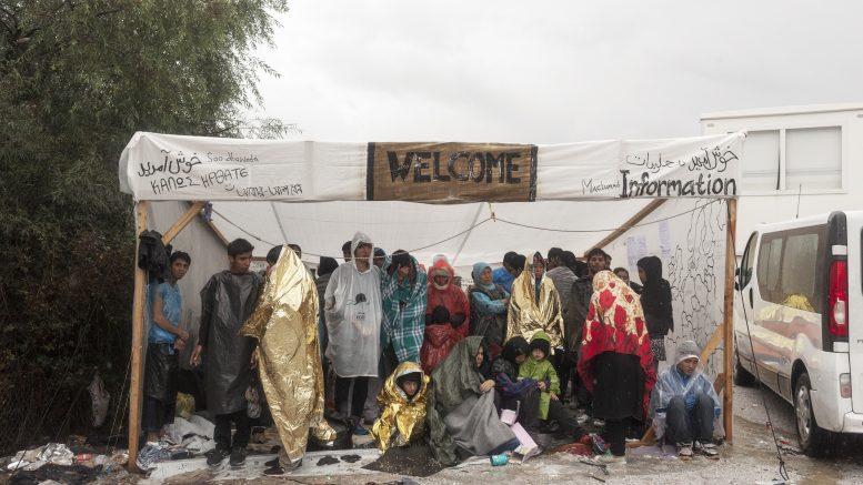 """Πρόσφυγες βρίσκουν καταφύγιο εν μέσω καταιγίδας καθώς περιμένουν να καταχωρηθούν στο Κέντρο Υποδοχής της Μόρια στη Λέσβο. ΓΧΣ: """"H Ευρώπη έχει κάνει μια φρικτή δουλειά. Υποδέχεται τους πρόσφυγες με ανύψωση φρακτών με αγκαθωτά συρματοπλέγματα καθώς και παροχή εντελώς ακατάλληλων συνθηκών υποδοχής""""                          photo ©Alessandro Penso, Μόρια, Λέσβος"""