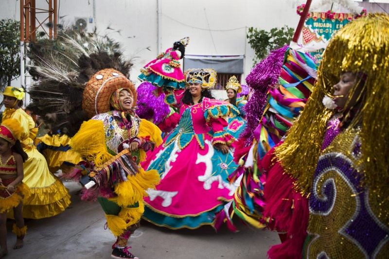 Women dance maracatu de baque, an Afro-Indigenous dance usually performed during Carnival, at the Associação das Mulheres, in Nazare da Mata, in the state of Pernambuco, Brazil, on Sunday, Nov. 17, 2014. The dance is typically performed by all men, usually sugarcane workers, but at the women's organization the dancers make-up the first and only all-female group. It represents the crowning of an African slave King and Queen as a way to preserve African culture and heritage. Photo by: Lianne Milton / UN Women
