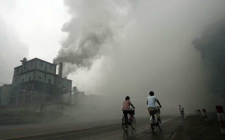 (FILES) - This photo taken on July 18, 2006 shows cyclists passing through thick pollution from a factory in Yutian, 100km east of Beijing in China's northwest Hebei province. Surging levels of carbon dioxide sent greenhouse gases in the atmosphere to a new record in 2013, while oceans, which absorb the emissions, have become more acidic than ever, the UN said on September 9, 2014. AFP PHOTO / PETER PARKS