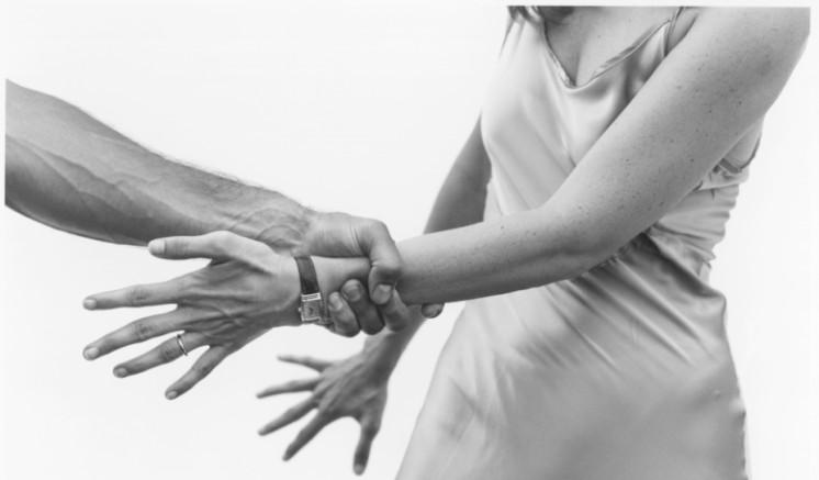 Man grabbing a woman's arm