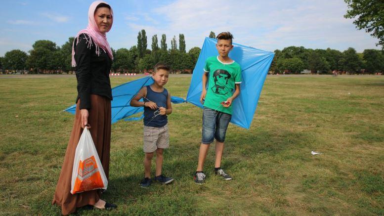 Μια μητέρα και οι δύο γιοι της, 7 και 13 ετών, πετούν χαρταετούς στο πρώην αεροδρόμιο - τώρα δημόσιο πάρκο - Tempelhof Airport στο Βερολίνο. Το πρώην αεροδρόμιο είναι τώρα καταυλισμός προσφύγων, όπου αυτή η οικογένεια έχει ζήσει για τους τελευταίους επτά μήνες μετά τη διαφυγή της από τον πόλεμο στο Αφγανιστάν. Image: Courtesy of Save the Children