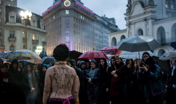 """Στην Αργεντινή, μια γυναίκα στέκεται ημίγυμνη με το μήνυμα """"Αυτό το σώμα δολοφονείται."""" Photo: Cobertura Colaborativa NosotrasParamos"""