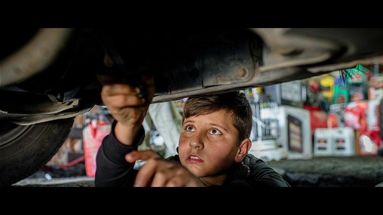 O Mohammed, 14 ετών, Σύριος πρόσφυγας από το Kobani, επισκευάζει αυτοκίνητο σε ένα συνεργείο στο Erbil του Iraq τον Μάρτιο του 2016. Μελέτη της ΔΟΕ δείχνει πώς υφίσταται μία σημαντική συσχέτιση μεταξύ παιδικής εργασίας και καταστάσεων συγκρούσεων και καταστροφών. UNICEF/UN020145/Yar